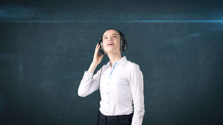 earbud: Businesswoman in white skirt relaxing listening to music on stereo headphones with blissful smile. Background isolated . Stock Photo