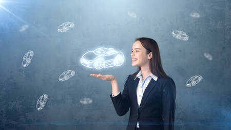 businessperson: Portrait of young woman holding painted cartoon car on the open hand palm, drawn studio background. Business concept.