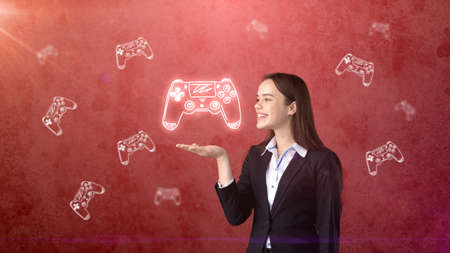gamers: Portrait of young woman holding gamers joystick on the open hand palm, over drawn studio background. Business concept.