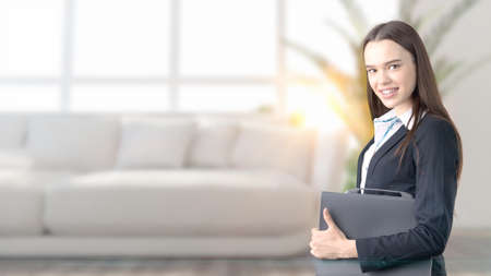 Young beautiful business woman and creative designer standing over blured interior background. Concepr of succesful architect Stock Photo