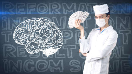 money packs: Beautiful medical woman doctor in uniform. Studio painted background. Concept of profitable health care.