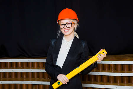 Beautiful blonde businesswoman with application tier at loft office in orange construction helmet and suit. Stock Photo
