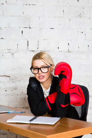 Young blond beauty businesswoman sitting at a office table with laptop, notebook and glasses in suit and boxing gloves. Stock fotó