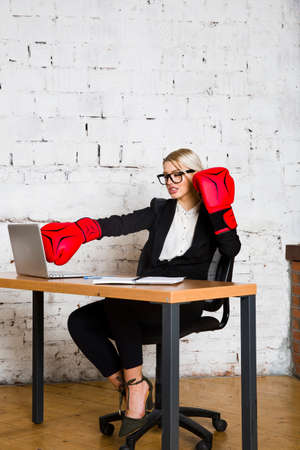 Young blond beauty businesswoman sitting at a office table with laptop, notebook and glasses in suit and boxing gloves. 版權商用圖片