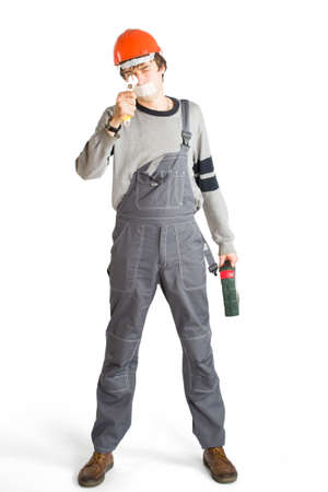 A young man in working grey clothes and orange hard helmet man with tape over mouth. Isolated on white background. Stock Photo