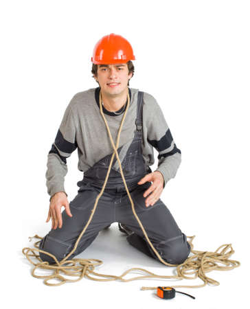 A young worker in grey uniform tied up with rope on white isolated background.