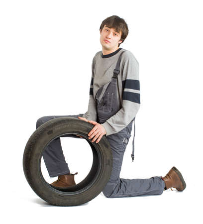 A young brunet foreman in working grey uniform with black wheel. Reklamní fotografie