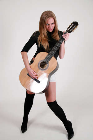 jamming: attractive blond woman jamming out on the guitar