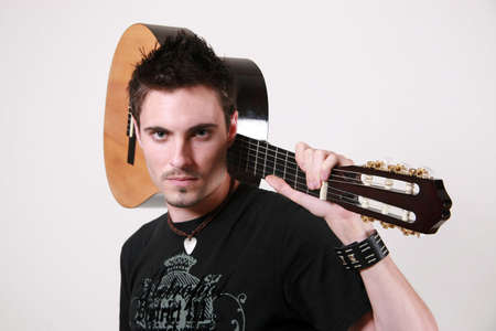 young scruffy male guitarist posing with acoustic guitar