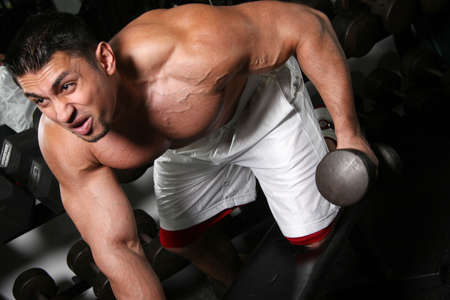 curls: A young handsome tone muscular male curling dumbell Stock Photo