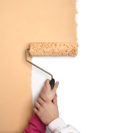 Un pareja pinta la pared con una brocha gorda usando sus manos