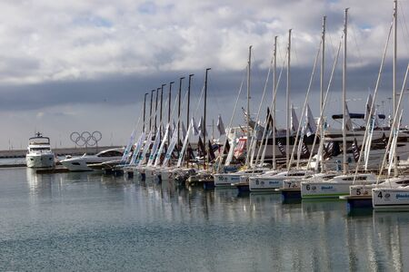 SOCHI, RUSSIA - November 06, 2015: The mooring with catamarans and boats against an emblem of the Olympic Games and the gray sky. Sochi, Russia Editorial