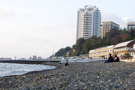 storey: SOCHI, RUSSIA - November 06, 2016: The sea stone beach against modern multi-storey buildings and hotels. Sochi, Russia
