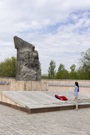 stele: VOLGOGRAD, RUSSIA - May 08, 2016: The person and the Monument to the soldiers of the Volgograd garrison who have been killed in battles in the territory of Chechnya. Zhukov Ave., Volgograd, Russia