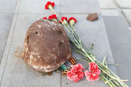 TAGANROG, RUSSIA - July 19, 2016: The soldiers helmet of times of World War II, lies at a monument devoted to Muisky heights. Taganrog, Russia Editorial