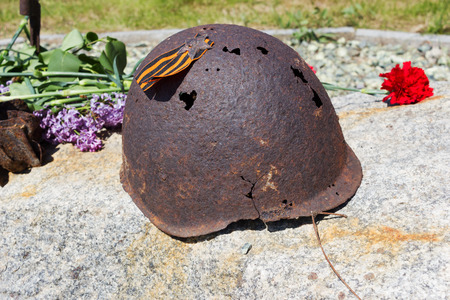 VOLGOGRAD, RUSSIA - May 04, 2016: An old rusty helmet of the Soviet soldier who was at war in the years of World War II, a red flower, the St.Georges Ribbon. Volgograd, Russia Editorial