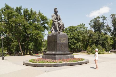 anton: TAGANROG, RUSSIA - June 23, 2016: The monument to Anton Pavlovich Chekhov, sits on a chair, on a stone pedestal, in park, against the blue sky. Taganrog, Russia