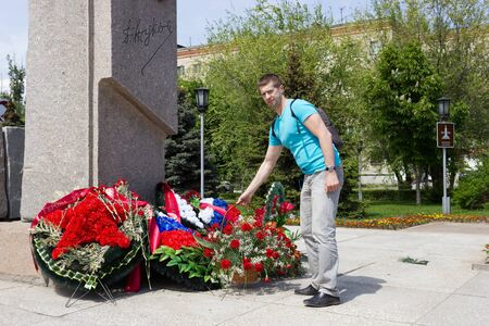 stele: VOLGOGRAD, RUSSIA - May 05, 2016: The man puts, puts a flowers basket before a monument to the hero of World War II Zhukov. Volgograd, Russia