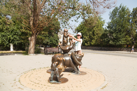 TAGANROG, RUSSIA - June 23, 2016: The girl attentively considers, touches the Monument to literary characters from books and stories of Chekhov, in the form of a cat, a dog, babbling and pigs. Russia Editorial