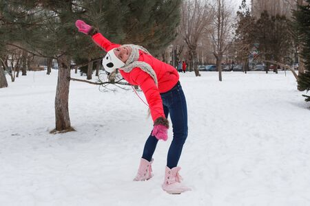 The girl in the winter on the street in a red jacket, a cap and a scarf, in the park against the background of snow, has bent back