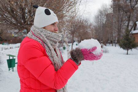 The girl in the winter on the street in a red jacket, a cap and a scarf, in the park against the background of snow, holds snow in hand