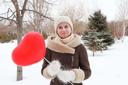 The girl in winter clothes keeps the red balloon in the form of heart in the park in the winter in the middle of snow