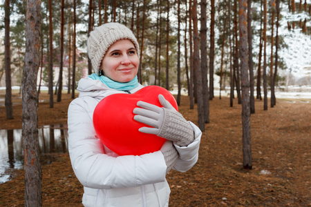 The woman in the middle of trees keeps in warm clothes naduveny the balloon in the form of heart Stock Photo