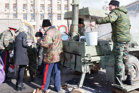 civilian: VOLGOGRAD, RUSSIA - February 26, 2017: People in a military uniform, military near the field kitchen distribute to the civilian population food