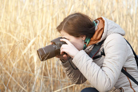 The girl the photographer holds the camera in the middle of dry plants and bushes Banco de Imagens - 76779385