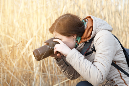 The girl the photographer holds the camera in the middle of dry plants and bushes Banco de Imagens - 76779514