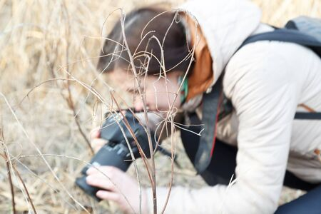 The girl the photographer holds the camera in the middle of dry plants and bushes Banco de Imagens