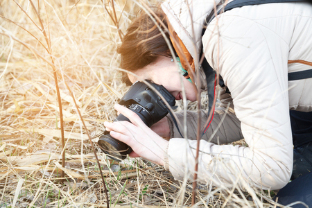 The girl the photographer holds the camera in the middle of dry plants and bushes Banco de Imagens - 76779404