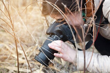 The girl the photographer holds the camera in the middle of dry plants and bushes Banco de Imagens - 76779402