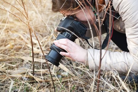 The girl the photographer holds the camera in the middle of dry plants and bushes Banco de Imagens - 76779389