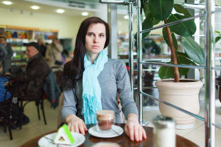 The girl misses in cafe (restaurant) at a table with a coffee mug Stock Photo