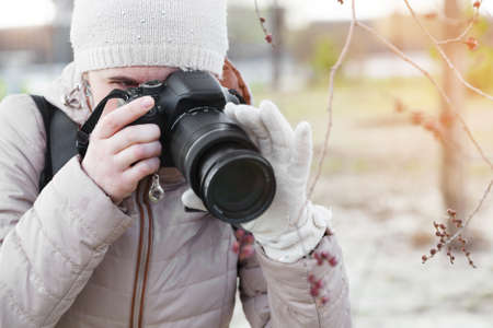 The girl the photographer keeps the camera before herself hands in gloves