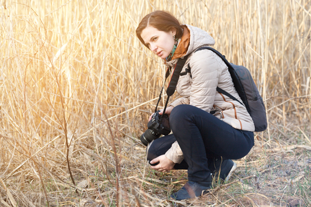 The girl the photographer holds the camera in the middle of dry plants and bushes Stock Photo