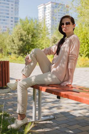 La jeune fille, la brune dans une veste rose dans la rue dans le parc se trouve sur un banc l'après-midi dans le parc Banque d'images - 80275733