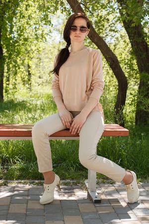 La jeune fille, la brune dans une veste rose dans la rue dans le parc se trouve sur un banc l'après-midi dans le parc Banque d'images - 80275724
