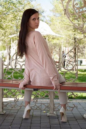 La jeune fille, la brune dans une veste rose dans la rue dans le parc se trouve sur un banc l'après-midi dans le parc Banque d'images - 80275741