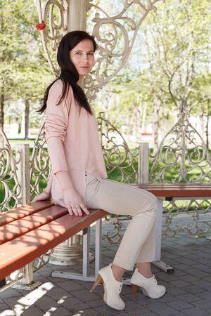 La jeune fille, la brune dans une veste rose dans la rue dans le parc se trouve sur un banc l'après-midi dans le parc Banque d'images - 80276376