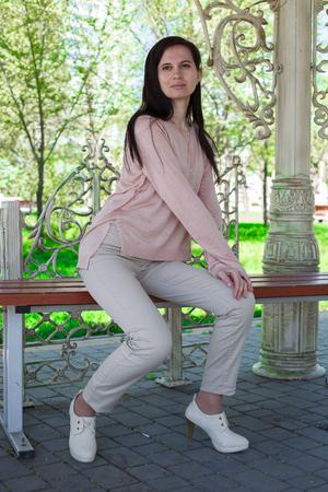 La jeune fille, la brune dans une veste rose dans la rue dans le parc se trouve sur un banc l'après-midi dans le parc Banque d'images - 80276403