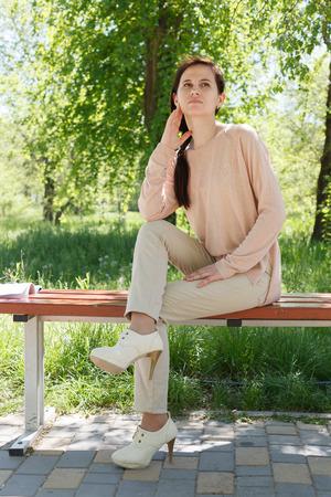 La jeune fille, la brune dans une veste rose dans la rue dans le parc se trouve sur un banc l'après-midi dans le parc Banque d'images - 80425568