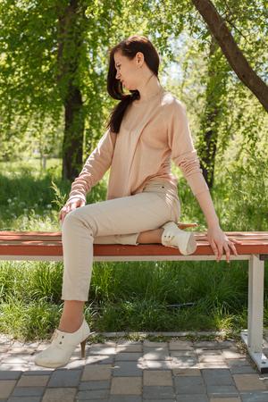 La jeune fille, la brune dans une veste rose dans la rue dans le parc se trouve sur un banc l'après-midi dans le parc Banque d'images - 80425570