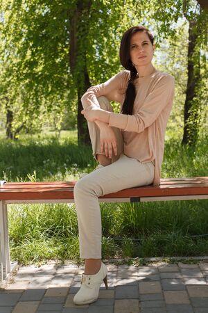 La jeune fille, la brune dans une veste rose dans la rue dans le parc se trouve sur un banc l'après-midi dans le parc Banque d'images - 80425582