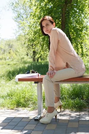 La jeune fille, la brune dans une veste rose dans la rue dans le parc se trouve sur un banc l'après-midi dans le parc Banque d'images - 80425586