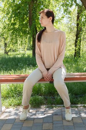 La jeune fille, la brune dans une veste rose dans la rue dans le parc se trouve sur un banc l'après-midi dans le parc Banque d'images - 80437806
