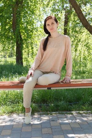 La jeune fille, la brune dans une veste rose dans la rue dans le parc se trouve sur un banc l'après-midi dans le parc Banque d'images - 80437809