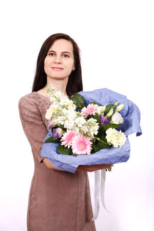 perishable: Portrait of the girl of the brunette with perishable hair in a beige dress on a white background with a bouquet of flowers