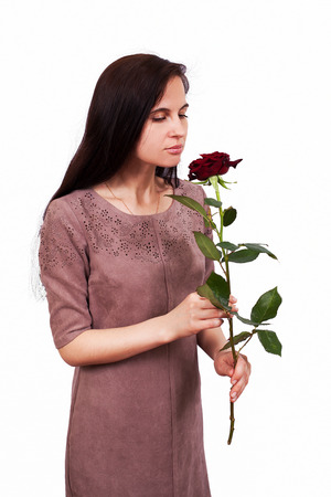 perishable: Portrait of the girl of the brunette with perishable hair in a beige dress on a white background with a red, claret rose